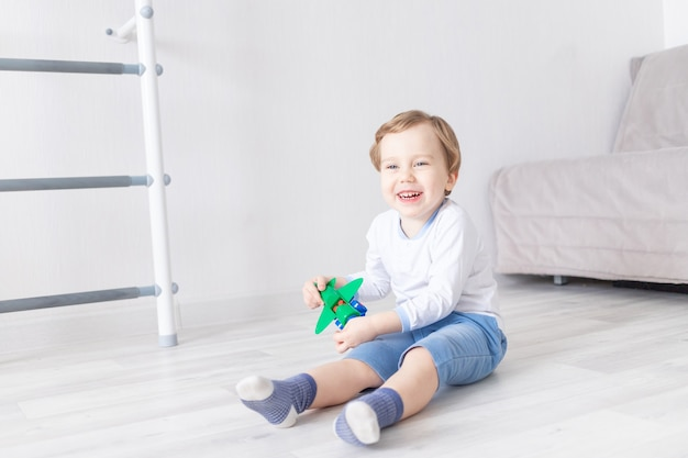 Happy baby boy plays at home with an airplane and laughs