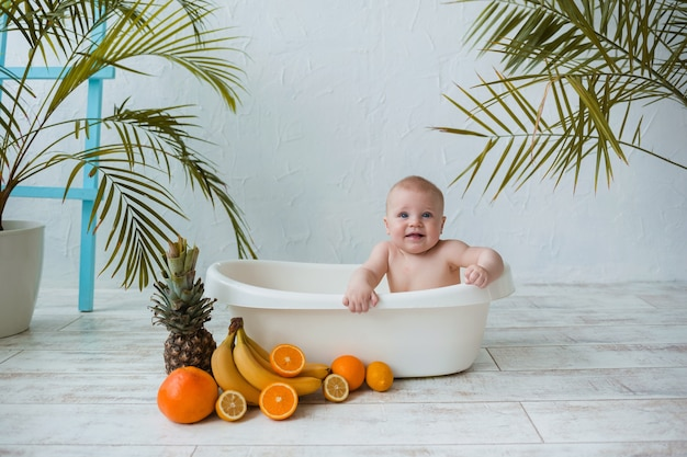 Happy baby boy sits in a white tub with tropical fruits on a white surface with plants with space for text