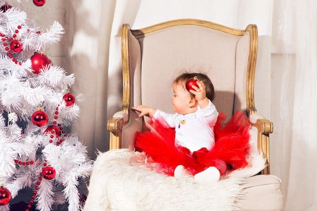 Счастливый малыш девочка возле елки