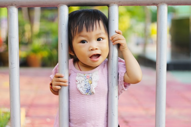 Happy baby child girl standing and holding a steel fence.
