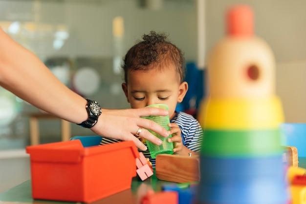 幸せな赤ちゃんは水を飲み、幼稚園でおもちゃのブロックで遊んでいます。