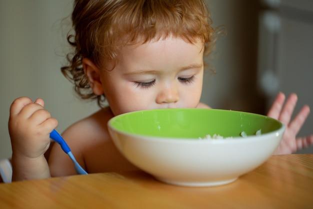숟가락으로 자신을 먹는 행복한 아기.