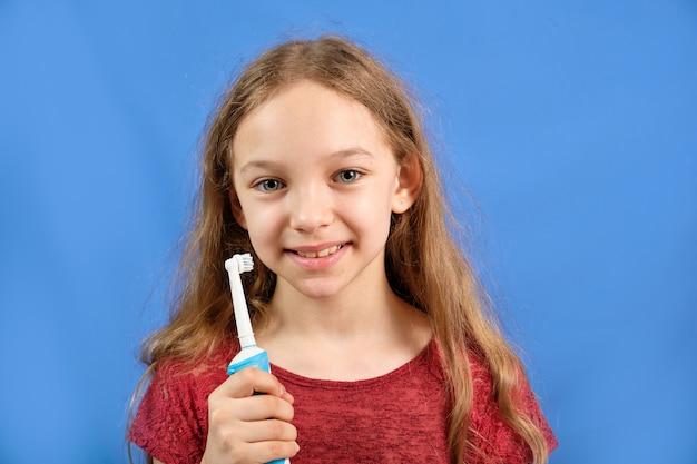 Счастливая девочка чистит зубы зубной щеткой