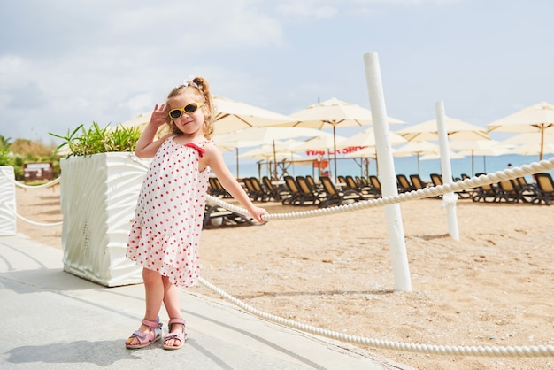 Happy baby girl in a dress on the beach by the sea in summer.