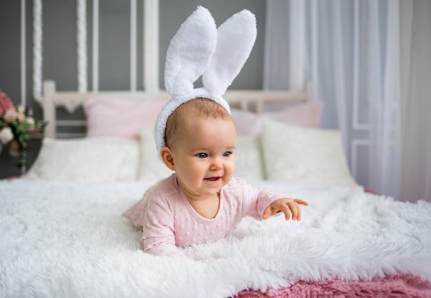 분홍색 드레스에 행복한 아기 소녀와 토끼 귀를 가진 머리띠가 방에있는 침대에서 크롤링됩니다. 아동 성장