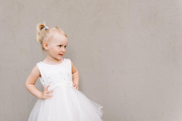 灰色の壁に白いドレスでハッピーベビー女の子