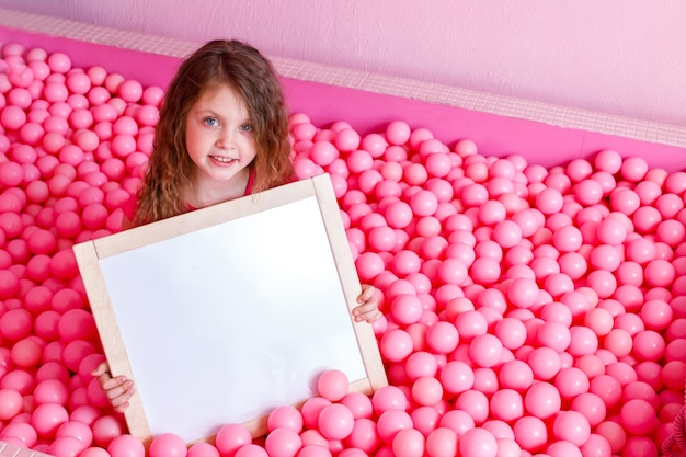 Счастливая девочка сидит в маленьких пластиковых розовых воздушных шарах и держит пустую доску для рисования