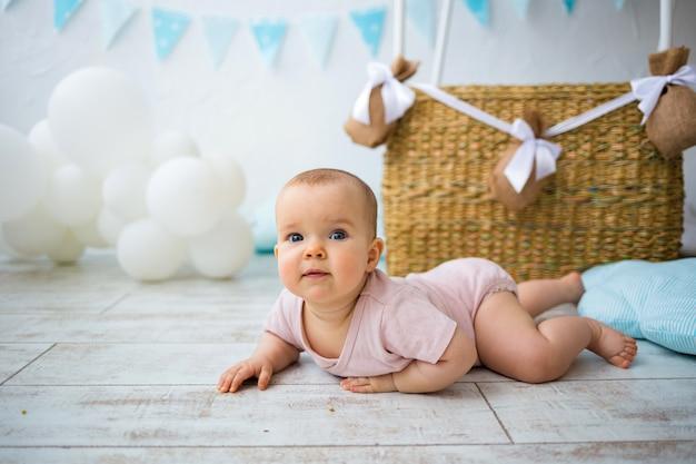 Happy baby girl lies near a wicker basket on a white background