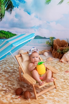 Happy baby girl lies on a wooden deck chair, sunbathes on a sandy beach with palm trees by the sea