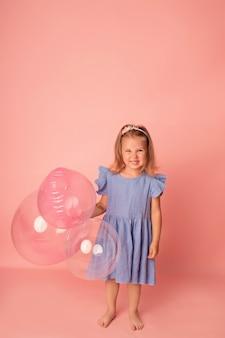 Счастливая девочка на розовом фоне с воздушными шарами. праздник. день рождения