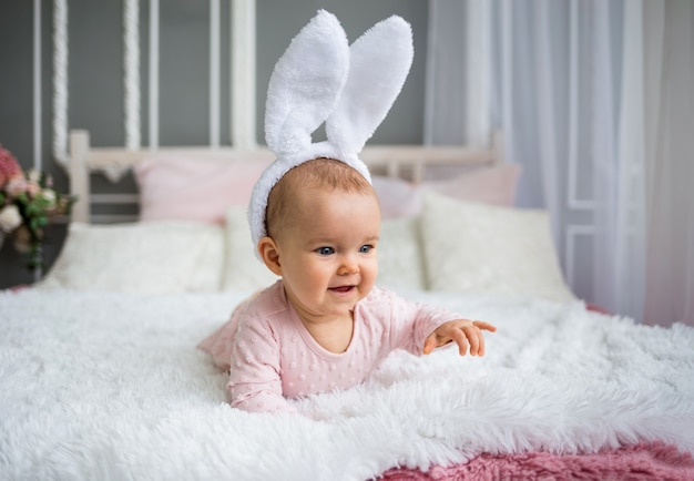 Happy baby girl in a pink dress and a headband with bunny ears is crawling on the bed in the room. child growth