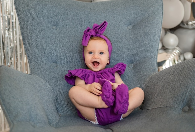 Happy baby girl in a purple bandage sitting in a gray chair