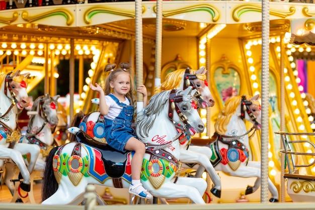 행복한 아기 소녀는 여름에 놀이공원에서 말을 타고 회전목마를 탄다