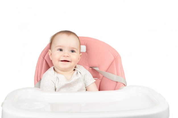 Happy baby girl sitting in a high chair and smile isolated on white background