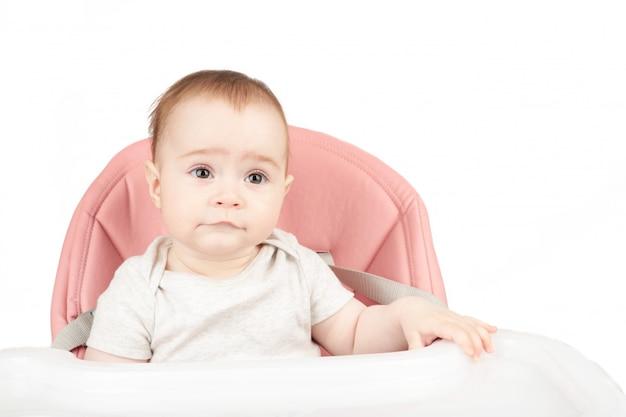 Счастливый ребёнок сидя в высоком стуле изолированном на белизне