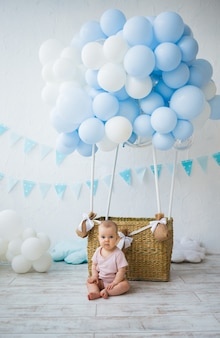 Happy baby girl sitting near a wicker basket with balloons on a white background