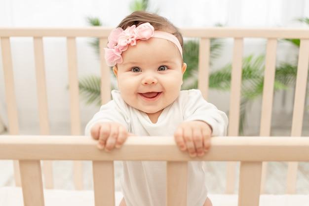 Счастливая девочка шесть месяцев стоя в кроватке