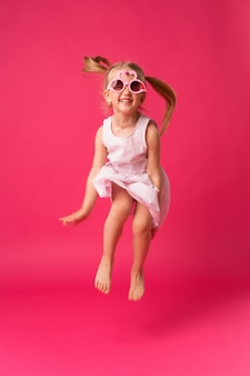 Happy baby girl smiling in sunglasses on pink background
