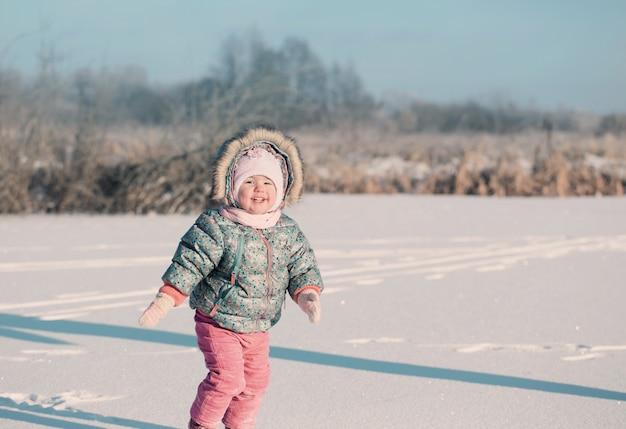 Happy baby girl on snow