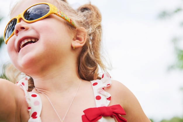 Happy baby girl in a summer sunglasses.