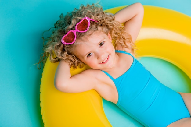 Happy baby girl in swimsuit with circle isolated on blue background