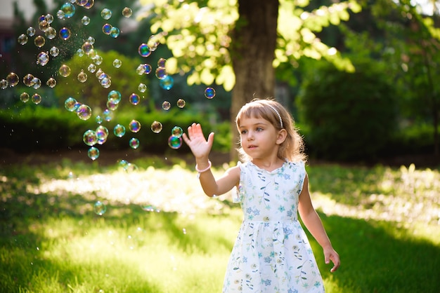 Happy baby girl with heterochromia two colored eyes standing in grass with dandelions at sunny summer evening. child outdoors in nature at sunset blowing bubbles