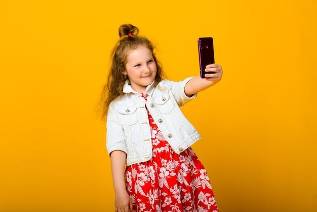 Happy baby girl with phone isolated on yellow