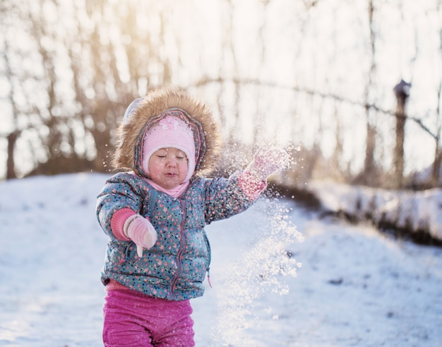 Happy baby girl with snow