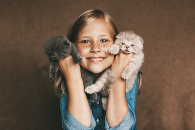 Happy baby holding beautiful british kittens