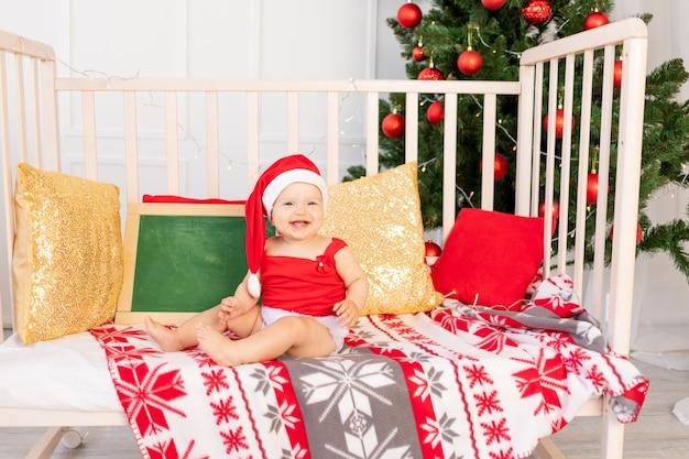 크리스마스 트리 옆에 집에서 침대에 앉아 산타 모자에 행복한 아기