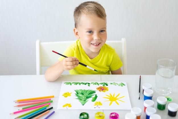 행복한 아기 아이는 흰 종이에 밝은 색 페인트가 있는 브러시로 그림을 그리고 미소를 짓습니다