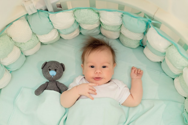 Happy baby lies on his back in a white round bed in the bedroom with toys.