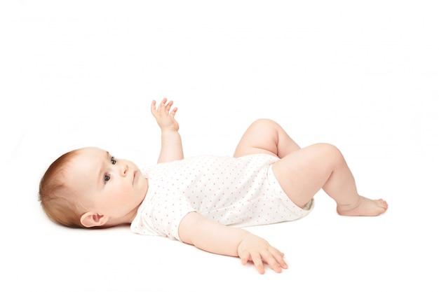 Счастливый лежать младенца изолированный на белой предпосылке.