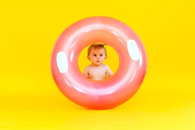수영 서클이 있는 10개월의 행복한 아기는 노란색 배경에 앉아 있고, 수영 서클에 있는 아기의 스튜디오 사진