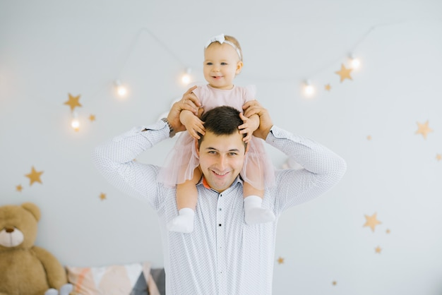 Happy baby one-year-old girl sits on dad's shoulders and they smile in the children's room decorated with glowing stars on the walls