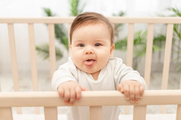 Счастливый ребенок показывает язык, стоя в кроватке