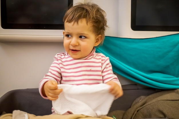 Happy baby sit in baby bassinet of airplane laugh and hold a wet hot towel for washing hands