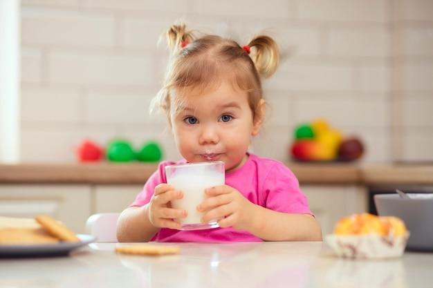 キッチンのテーブルに座って食欲をそそる幸せな赤ちゃん