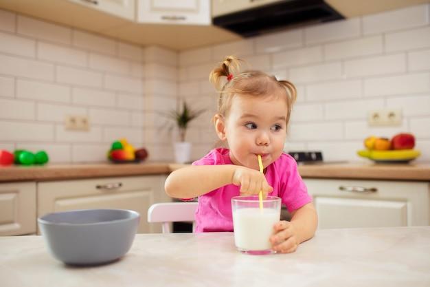 부엌에서 테이블에 앉아 식욕으로 먹는 행복한 아기