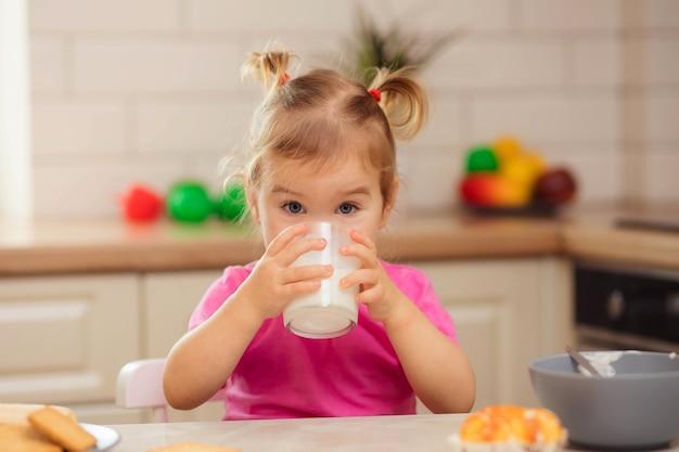 Счастливый ребенок сидит за столом на кухне и ест с аппетитом