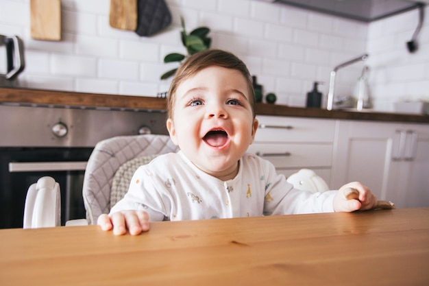 Happy baby sitting in high chair and laughing in a modern white kitchen.