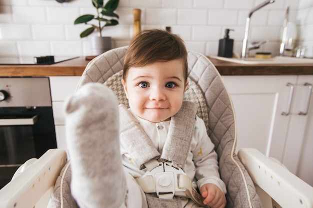 Happy baby sitting in high chair in a white kitchen.