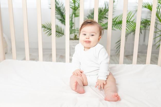 Счастливый ребенок сидит в кроватке в белом боди
