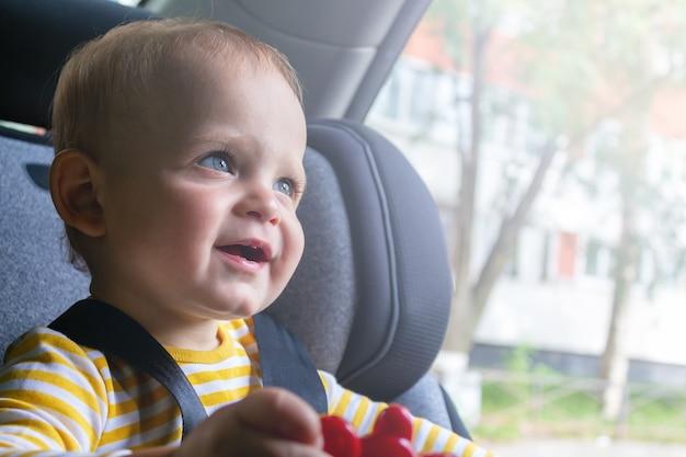 Счастливый ребенок сидит в автокресле, играя