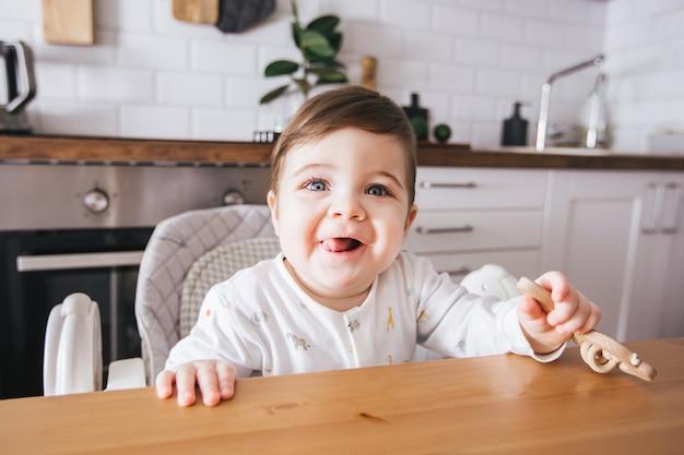 높은 의자에 앉아 현대 흰색 부엌에서 웃고 행복한 아기. 아이들을위한 건강한 영양. 귀여운 유아 측면보기