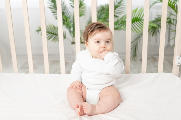 Счастливый ребенок сидит в кроватке в белом боди и сосет палец