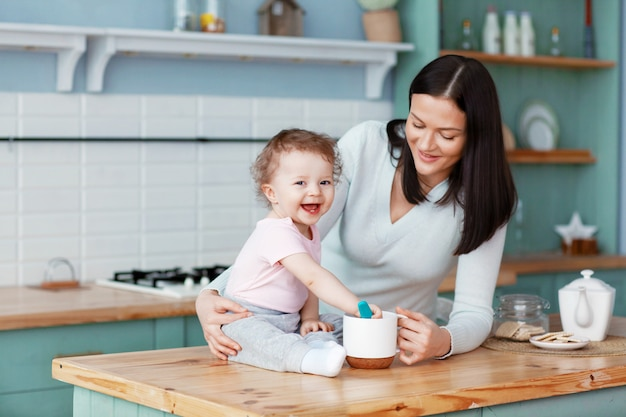 Happy baby sitting on the kitchen table with mom stirring porridge with a spoon
