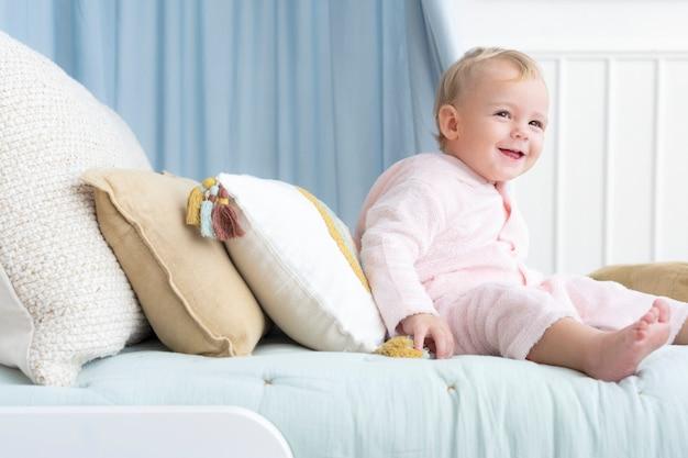 침대에 앉아서 웃고 있는 행복한 아기