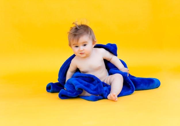 노란색 배경에 앉아 있는 행복한 아기는 후드가 있는 파란색 수건에 싸여 있습니다. 목욕 후 아기.
