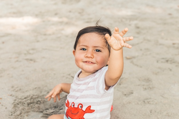 Happy baby sitting on sand